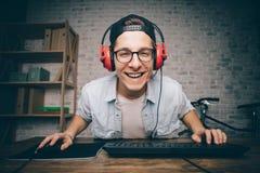 Hombre joven que juega al juego en casa y que fluye el vídeo del playthrough o del recorrido Imágenes de archivo libres de regalías