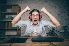 Hombre joven que juega al juego en casa y que fluye el vídeo del playthrough o del recorrido Fotografía de archivo libre de regalías