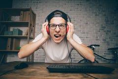 Hombre joven que juega al juego en casa y que fluye el vídeo del playthrough o del recorrido Fotos de archivo