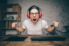 Hombre joven que juega al juego en casa y que fluye el vídeo del playthrough o del recorrido Imagen de archivo