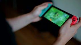 Hombre joven que juega al juego en el interruptor de Nintendo almacen de metraje de vídeo