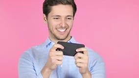 Hombre joven que juega al juego en Smartphone en fondo rosado almacen de metraje de vídeo