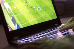 Hombre joven que juega al videojuego con el ordenador portátil Fútbol en línea Fotos de archivo libres de regalías