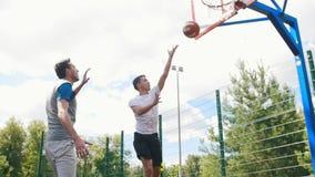 Hombre joven que juega a baloncesto al aire libre con el amigo y que anota meta almacen de video