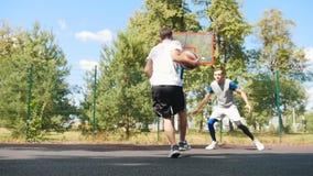 Hombre joven que juega a baloncesto al aire libre con la meta del amigo, del goteo y el anotar almacen de video