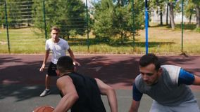 Hombre joven que juega a baloncesto al aire libre con los amigos y que intenta anotar la meta - llevar la bola almacen de metraje de vídeo