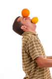 Hombre joven que juega con el limón y la naranja Imagen de archivo