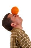 Hombre joven que juega con la naranja Foto de archivo libre de regalías
