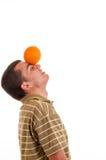 Hombre joven que juega con la naranja Fotografía de archivo