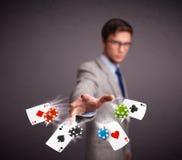 Hombre joven que juega con las tarjetas y los microprocesadores del póker Fotografía de archivo