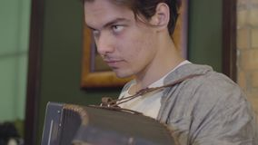 Hombre joven que juega el acorde?n Música alegre en el instrumento viejo Concepto popular metrajes