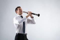 Hombre joven que juega el clarinete Imagen de archivo libre de regalías