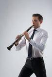 Hombre joven que juega el clarinete Imagenes de archivo