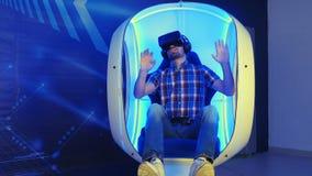 Hombre joven que juega el videojuego en simulador de la realidad virtual 3D Imagenes de archivo