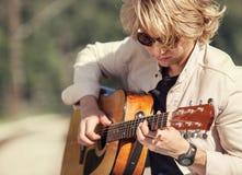 Hombre joven que juega en el retrato de la guitarra Imágenes de archivo libres de regalías