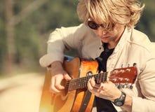 Hombre joven que juega en el retrato de la guitarra Fotos de archivo