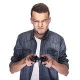 Hombre joven que juega en la consola o el ordenador Foto de archivo