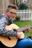Hombre joven que juega en la guitarra acústica Imagen de archivo