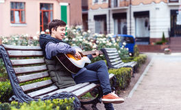 Hombre joven que juega en la guitarra acústica al aire libre Imagenes de archivo