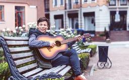 Hombre joven que juega en la guitarra acústica al aire libre Fotos de archivo libres de regalías