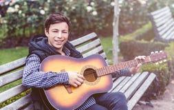 Hombre joven que juega en la guitarra acústica al aire libre Foto de archivo libre de regalías