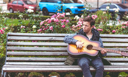 Hombre joven que juega en la guitarra acústica al aire libre Imagen de archivo libre de regalías