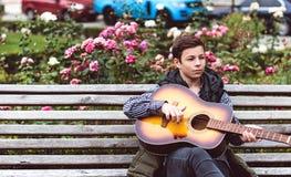 Hombre joven que juega en la guitarra acústica al aire libre Imágenes de archivo libres de regalías
