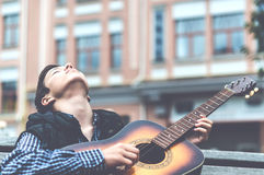 Hombre joven que juega en la guitarra acústica al aire libre Fotos de archivo