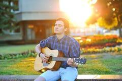 Hombre joven que juega en la guitarra acústica en parque Foto de archivo