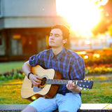 Hombre joven que juega en la guitarra acústica en un parque del verano Imagen de archivo