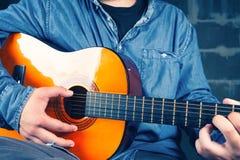 Hombre joven que juega en una guitarra Fotos de archivo libres de regalías