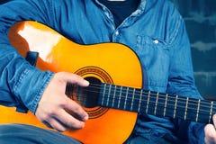 Hombre joven que juega en una guitarra Fotografía de archivo