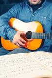 Hombre joven que juega en una guitarra Foto de archivo libre de regalías