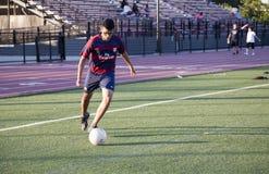 Hombre joven que juega a fútbol Foto de archivo libre de regalías
