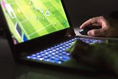 Hombre joven que juega a fútbol o al partido de fútbol en línea con el ordenador portátil Foto de archivo