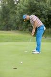 Hombre joven que juega a golf Imágenes de archivo libres de regalías