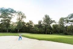 Hombre joven que juega a golf Foto de archivo libre de regalías