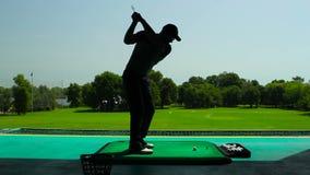 Hombre joven que juega a golf en la sombra almacen de video