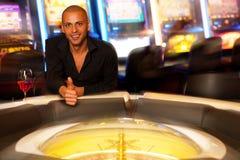 Hombre joven que juega la ruleta en dinero apostador y que gana del casino fotos de archivo libres de regalías