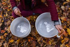 Hombre joven que juega los cuencos cristalinos al aire libre en el bosque en la caída 10/12 fotos de archivo