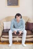 Hombre joven que juega a los videojuegos con la palanca de mando inalámbrica de Bluetooth Imagenes de archivo