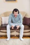 Hombre joven que juega a los videojuegos con la palanca de mando inalámbrica de Bluetooth Foto de archivo