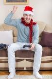 Hombre joven que juega a los videojuegos con la palanca de mando inalámbrica de Bluetooth Imagen de archivo libre de regalías