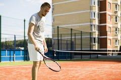 Hombre joven que juega a tenis en corte del patio trasero de la escuela imágenes de archivo libres de regalías