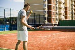 Hombre joven que juega a tenis en corte en el bloque de yarda de las viviendas al aire libre fotos de archivo