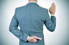 Hombre joven que jura un juramento, cruzando sus fingeres en el suyo detrás foto de archivo libre de regalías