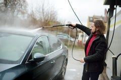 Hombre joven que lava su coche con la lavadora de alta presión fotografía de archivo libre de regalías