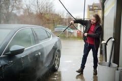 Hombre joven que lava su coche con la lavadora de alta presión imagen de archivo libre de regalías