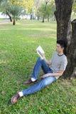 Hombre joven que lee el libro en el parque Imagen de archivo
