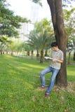Hombre joven que lee el libro en el parque Imagenes de archivo